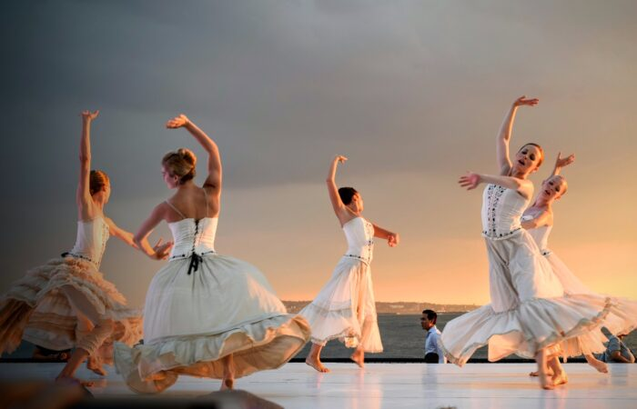 five women dancing top of gray stage