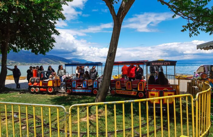 people riding on red and yellow roller coaster during daytime